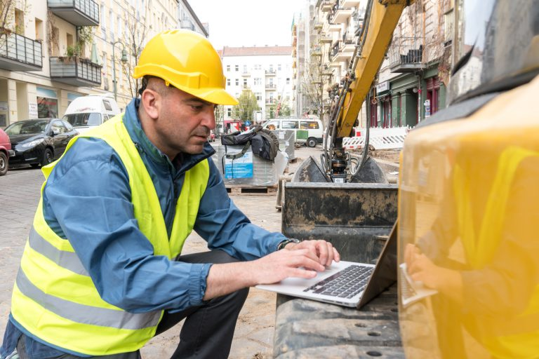 Construction Worker Using Laptop in the Construction Field