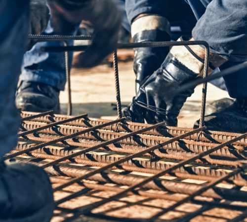 Construction workers handling rebar.