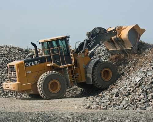 Bulldozer moving rock on site.