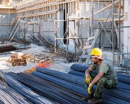 Construction Worker Sitting on Construction Materials