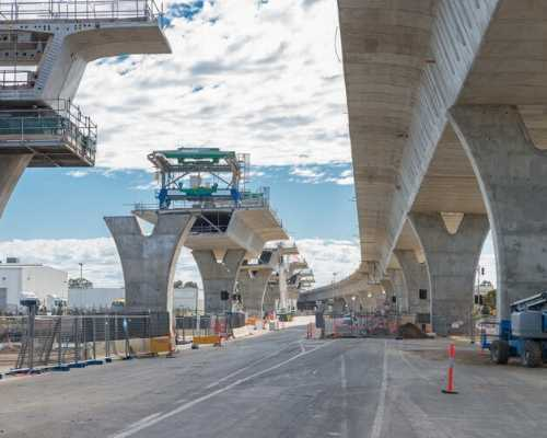 Construction workers building a large concrete bridge