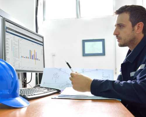 Construction worker looking at data on a computer.