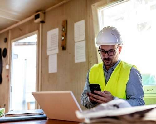 Construction worker on site using mobile device.